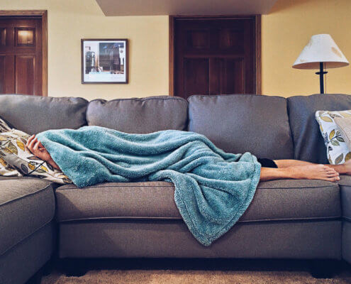 Man sleeping on a couch, hiding from his responsibilities